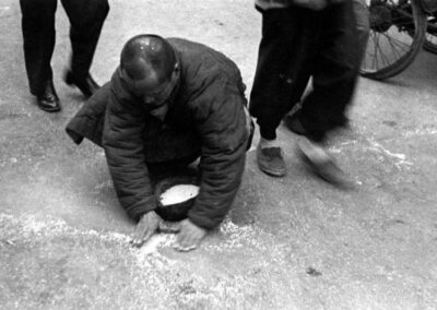 A poor man picking up spilled rice in the street, from Shanghai: 1949 The End of an Era, 1949