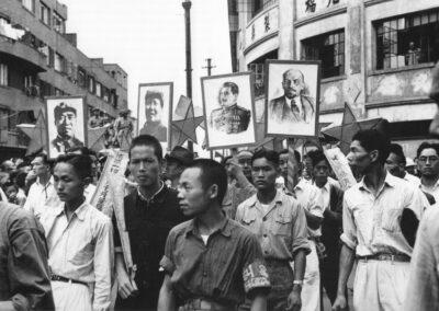 A crowd parading the portraits of Zhu De, Mao Zedong, Joseph Stalin and Vladimir Lenin, from Shanghai: 1949 The End of an Era, 1949.